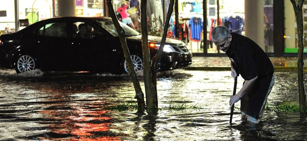 A store manager works to free a clogged storm sewer drain in a shopping center parking lot after a line of heavy rain moved through the area caused flooding in November 2015 in Atlanta.