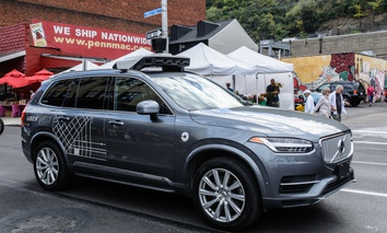 An Uber autonomous vehicle travels along Penn Avenue in Pittsburgh's Strip District.