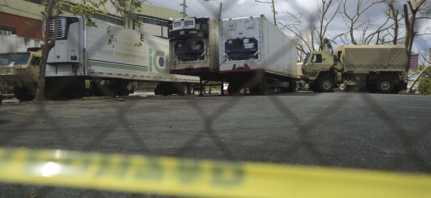 Three containers for holding corpses, right, are parked outside the Institute of Forensic Science, brought in to give support in the aftermath of Hurricane Maria in San Juan, Puerto Rico, Monday, Oct. 2, 2017.
