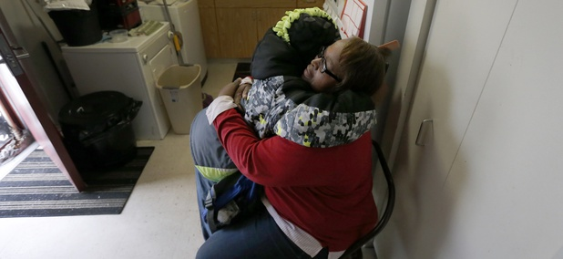 In this Jan. 29, 2016, photo, Debra Aldridge, right, hugs and recites a prayer with her grandson Mario Hendricks at her Chicago home. The number of children being raised by grandparents has spiked in recent years.
