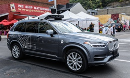 October 7, 2017, An Uber autonomous driving car, with back-up human driver aboard, navigates the Pittsburgh, Pennsylvania Strip District on a busy Saturday morning.