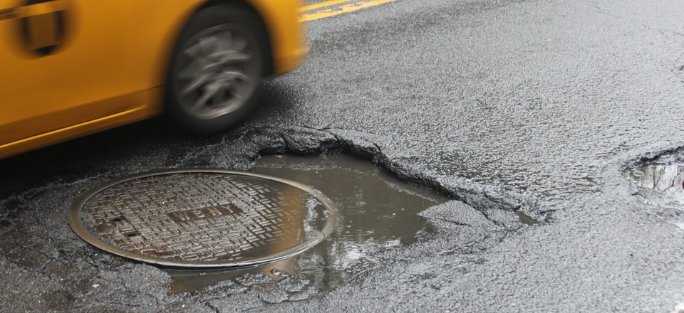 Taxi driving over big pothole in New York.