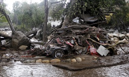 A car and debris smashed against a tree along Hot Springs Road in Montecito, Calif. Heavy rain brought flash flooding and mudslides to the area in Montecito, Calif. on Tuesday, January 9, 2018.