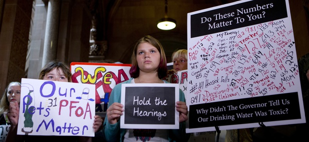 n this June 15, 2016 file photo, Hoosick Falls residents hold signs during a news conference at the state Capitol in Albany, N.Y., calling for hearings on the state's handling of PFOA contamination in drinking water in their town. New York environmental r