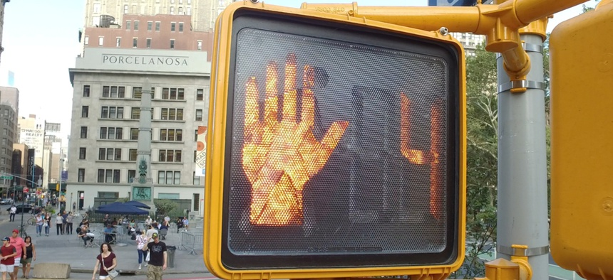 Crosswalk countdown signal in New York CIty illuminated to stop people for traffic to pass through intersection.
