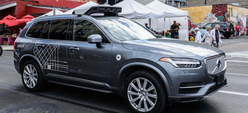 An Uber autonomous driving car, with back-up human driver aboard, navigates the Pittsburgh Strip District on a busy Saturday morning.