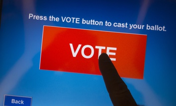 ARLINGTON, VIRGINIA, USA - November 5, 2013, voting on election day using electronic touch screen voting machine.