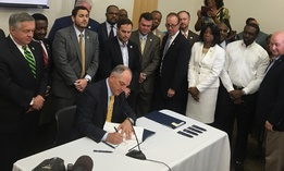 In this June 15, 2017 photo, a bipartisan group of lawmakers surround Louisiana Gov. John Bel Edwards as he signs 10 criminal justice bills into law during a ceremony in Baton Rouge, La.