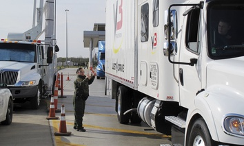 Border Patrol agent Gracie Briones waves through a tractor-trailer after it passed through an X-ray machine at the Laredo North checkpoint in Laredo, Texas, on Friday, February 2, 2018.