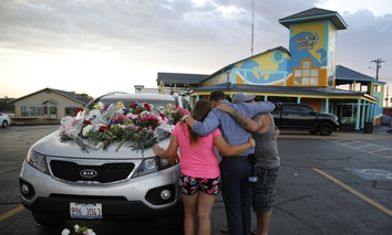 People pray by a car thought to belong to a victim of Thursday's boating accident before a candlelight vigil in the parking lot of Ride the Ducks Friday, July 20, 2018, in Branson, Mo. Seventeen people died when the boat capsized.