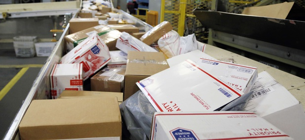 In this Dec. 14, 2017, file photo, packages travel on a conveyor belt for sorting at the main post office in Omaha, Neb.