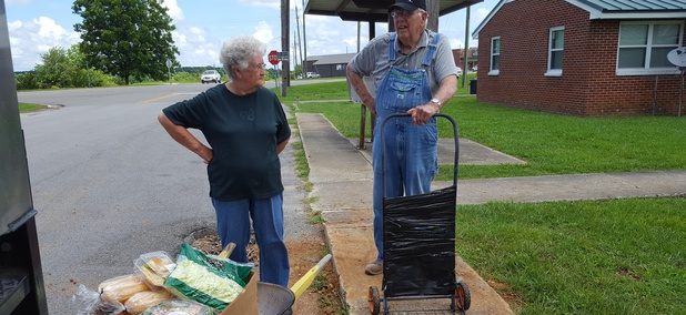 Nellie Allen, 81, left, and O'Neal West, 78, of Hackleburg, Alabama, load donated groceries into a wheelbarrow and a makeshift hand truck. They get food from the West Alabama Food Bank's mobile pantry every two weeks.