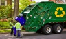 Workers empty recycling bins into a truck in a residential neighborhood in Arlington, Virginia.