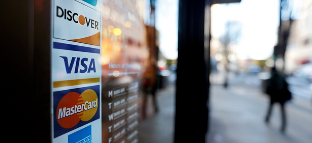 In this Jan. 31, 2018, file photo, credit card logos are posted to the door of a business in Atlanta.