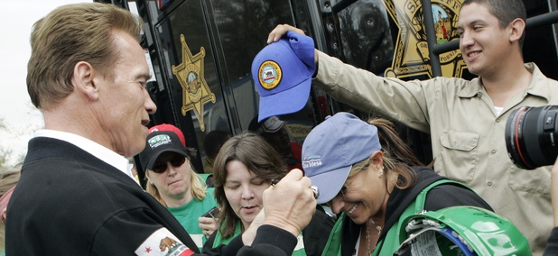 Then-California Gov. Arnold Schwarzenegger signs the cap of Cindy Brenneman, a Community Emergency Response Team (CERT) member after a news conference at the Santiago Fire Incident Command Post at Irvine Regional Park in Orange, Calif., Oct. 27, 2007.