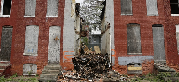 In this April 26, 2017 photo, debris remains where a demolished row house once stood in Baltimore, Maryland.