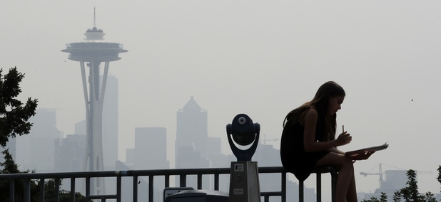 A girl works on a drawing next to an unused viewing scope as a smoky haze from wildfires obscures the Space Needle and downtown Seattle behind, Tuesday, Aug. 14, 2018.
