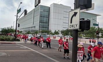 Arizona teachers in April dressed up in red shirts marching back from first day of Walk-Out known as RedForEd in Phoenix downtown along Jefferson Road.
