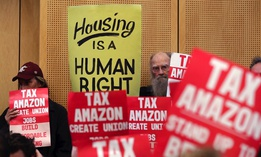 Members of the public look on at a Seattle City Council meeting before it voted in May to approve a tax on large businesses such as Amazon and Starbucks to fight homelessness.