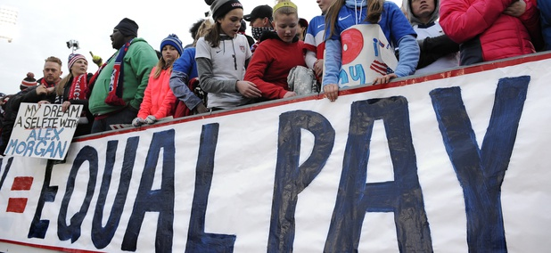 In this April 6, 2016, file photo, fans stand behind a large sign for equal pay for the women's soccer team during an international friendly soccer match between the United States and Colombia at Pratt & Whitney Stadium in East Hartford, Conn.