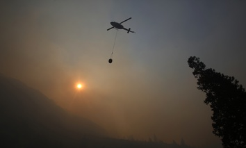 A fire helicopter takes off through smoke rising to make a drop on active fires in Yosemite National Park after the park reopened after a three week closure from smoke and fires on Tuesday, Aug. 14, 2018.