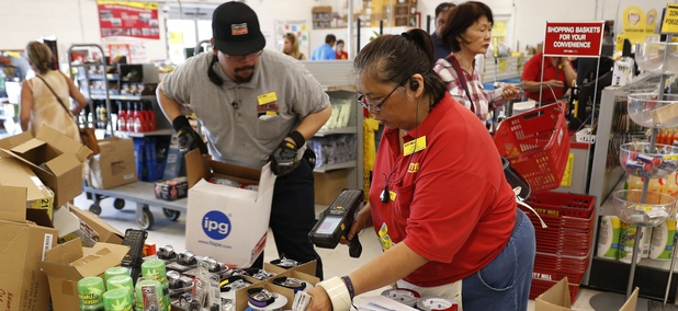 City Mill hardware store sales associates Frank Miller Gascon, left, Lisa Lavilla, fill a table up with duck tape, flashlights, and other hurricane supplies, Wednesday, Aug. 22, 2018, in Honolulu.