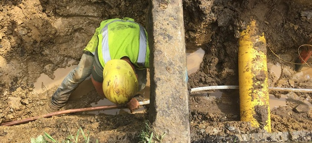After digging out the road and lawn, a worker ducks under the curb while connecting a copper pipe on private property with a Pex tube on public property.