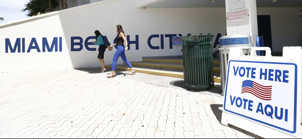 Pedestrians walk past a sign for a polling station at Miami Beach City Hall, Monday, Aug. 13, 2018, in Miami Beach, Fla.