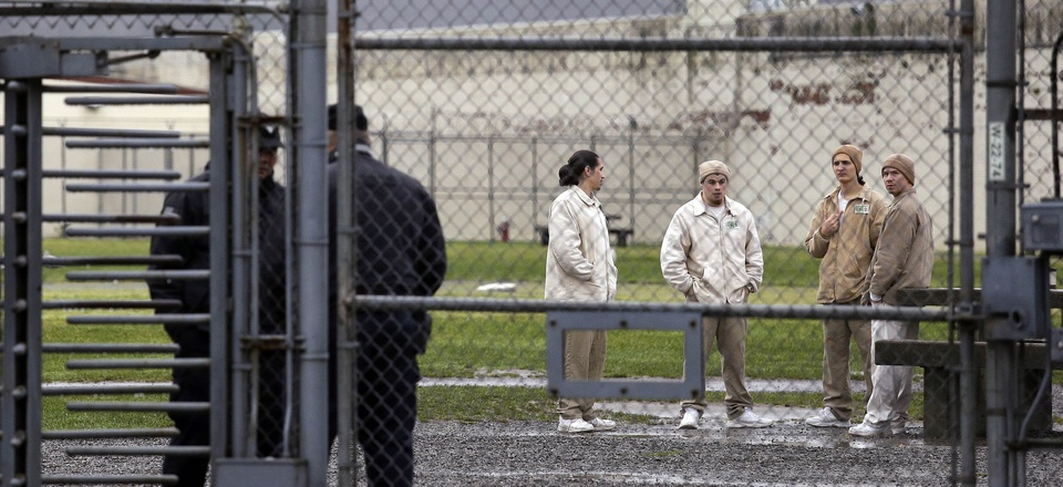 In this file photo taken Jan. 28, 2016, inmates mingle in a recreation yard in view of guards, left, at the Monroe Correctional Complex in Monroe, Wash.