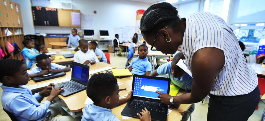 Teacher Denitra Henry, right, assists second grade student Jayden Bowie, with his computer during her math class at Turner Elementary School in southeast Washington, Tuesday, Aug. 29, 2017.