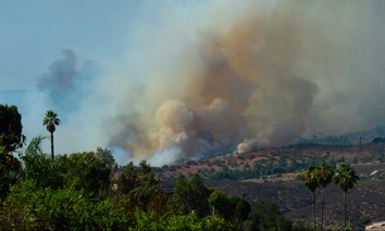 CalFire on July 29, 2018 battles wildfire as smoke rises near Fallbrook, California in San Diego County.