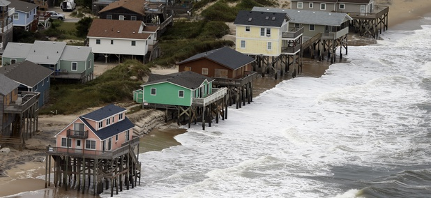 Oceanfront homes sit over the water as waves from hurricane Florence continue to pound the coast in Nags Head NC., Saturday, Sept. 15, 2018.