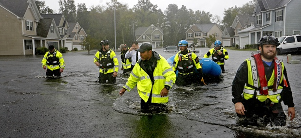 Members of the North Carolina Task Force urban search and rescue team wade through a flooded neighborhood looking for residents who stayed behind as Florence continues to dump heavy rain in Fayetteville, N.C. on Sunday.