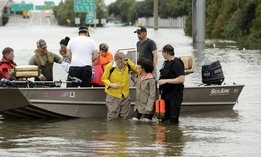 In this Aug. 27, 2017 file photo, residents are helped from a boat after being rescued from their flooded homes from Tropical Storm Harvey in Houston.