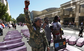Stevante Clark, left, brother of the late Stephon Clark, raises his fist in protest while standing among mock caskets, representing black people killed by California law enforcement, during a Sept. 18 demonstration in Sacramento.