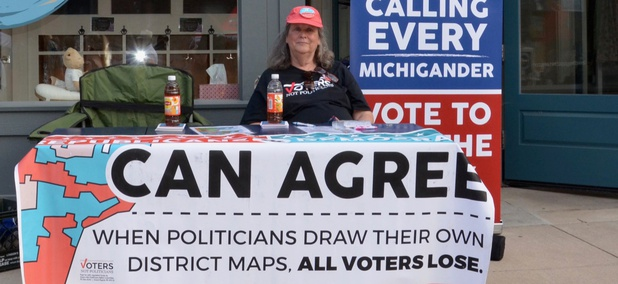A woman on July 12, 2018 staffs a booth in Chelsea, Michigan, supporting the group Voters not Politicians at the Chelsea Sounds and Sights on Thursday Nights festival.