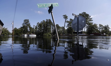 Street signs protrude through floodwaters in the aftermath of Hurricane Florence in Nichols, S.C., Friday, Sept. 21, 2018. Virtually the entire town is flooded and inaccessible except by boat, just two years after it was flooded by Hurricane Matthew.