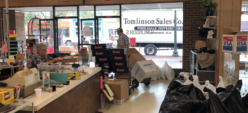 Employees at Tomlinson Department Store take all the merchandise out of the store in Georgetown, South Carolina, on Monday ahead of expected flooding.
