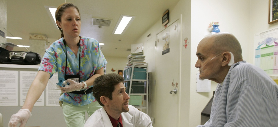 Dr. Joseph Bick, center, talks to Hepatitis C patient Richard Carreiro, as nurse Laura Escareno-Scarrott, watches in the hospice of the California Medical Facility in Vacaville, Calif., Jan. 17, 2007.
