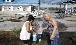 "Danny, right, and Gina Holland collect water in the aftermath of Hurricane Michael in Parker, Fla., Thursday, Oct. 11, 2018. ""We're running out of water,"" said Danny Holland of his neighborhood up the street that was damaged by the storm."