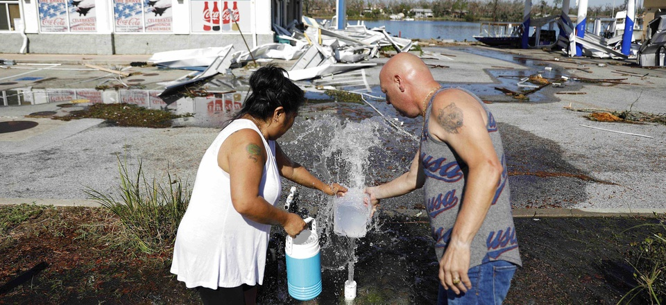 """Danny, right, and Gina Holland collect water in the aftermath of Hurricane Michael in Parker, Fla., Thursday, Oct. 11, 2018. """"We're running out of water,"""" said Danny Holland of his neighborhood up the street that was damaged by the storm."""