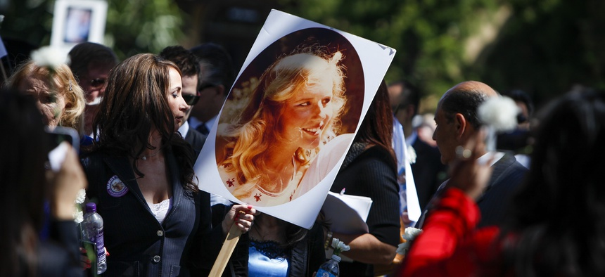 A woman holds a photo of Marsy Nicholas, whom Marsy's Law was named for, during a 2013 victims' rights march and rally in Santa Ana, California.