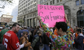 Shane Zaldivar holds up a sign as crowds jam a Super Bowl event in San Francisco. Zaldivar said the sign was a protest against the lack of affordable housing in the city.