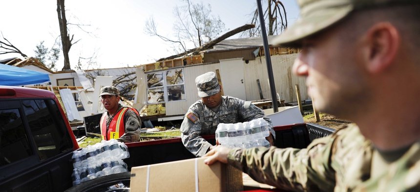 A damaged home stands in the background as soldiers with Florida National Guard's Bravo Company, 2nd Battalion, 124th Infantry Regiment, load food and water for the public at an aid distribution point in the wake of Hurricane Michael in Panama City, Fla.