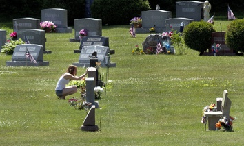 In this June 17, 2016 file photo, Erika Marble visits the gravesite of Edward Martin III, her fiancé and father of her two children, in Littleton, N.H. The 28-year old died Nov. 30, 2014, from an overdose of the opioid fentanyl.