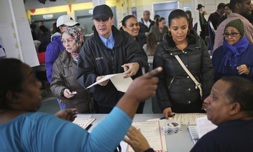 Voters get directions from poll workers at a polling station in the Washington Heights section of New York, Tuesday, Nov. 8, 2016.