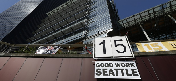 "A sign that reads ""15 Good Work Seattle"" is displayed below Seattle City Hall, right, and the Columbia Center building, left, Monday, June 2, 2014, after the Seattle City Council passed a $15 minimum wage measure."