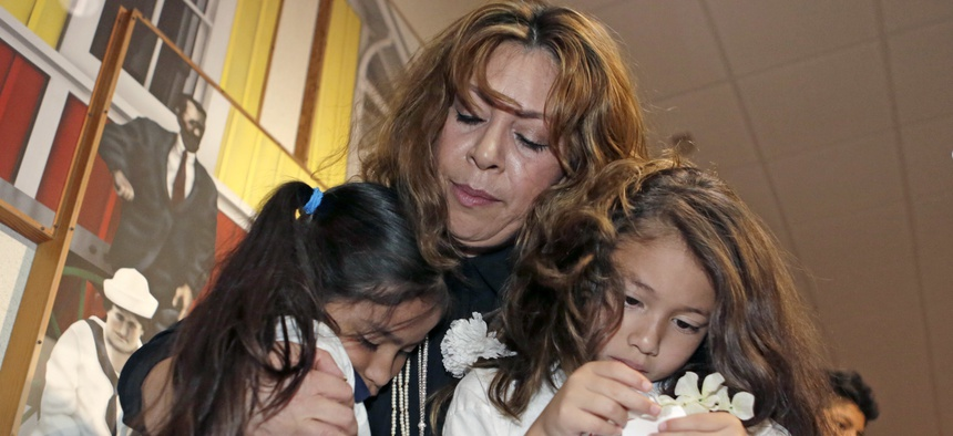 A woman comforts two children under her legal guardianship in Miami last year. One in five children being raised by extended family members live in an immigrant household, a new report shows.