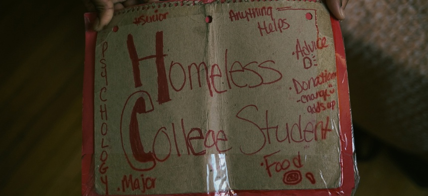 Bre, a homeless 24-year-old college student, holds the sign she previously used to ask for donations when she didn't have enough money to eat or take the bus to class at Trinity Washington University.