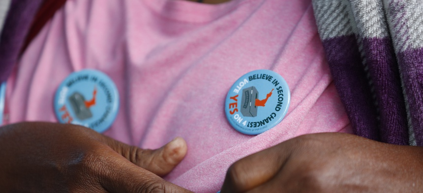 "In this, Monday, Oct. 22, 2018 photo, a woman puts on a pin-back button in support of Amendment 4 at the Ben & Jerry's ""Yes on 4"" truck in Miami."